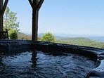 Step outside and enjoy the deluxe hot tub with its picturesque views of the woods and multi-layered mountains, and the...