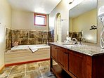 Relax in the spacious master en suite bathroom featuring a deep soaking jetted tub.