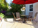 Private large and sunny patio with chairs, table and umbrella