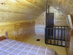 The cabin has a small upstairs loft bedroom.