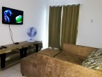 Sala de jantar e estar. Mesa acomoda 6 pessoas. TV, ventilador e sofá cama.