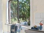 Sunshine through the bathroom window. Hidden laundry with washing machine and dryer.