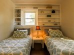 This guest bedroom has two twin size beds, a night stand with reading lamp, a ceiling fan and built-in bookshelves.