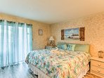The master bedroom is home to a balcony and king bed.