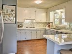 The fully equipped kitchen features modern tile backsplash and white cabinetry.