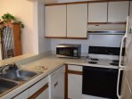 Fully stocked kitchen, including coffee maker, microwave, new chef's cutlery, and everything for cooking and serving