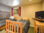 The kids will love the Where is Waldo wallpaper in this bedroom that contains two single beds.