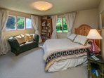 The second bedroom offers a comfy queen bed and views across the grassy yard to the water.