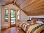 This bedroom features a king size bed under beautiful wood ceilings.