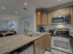Kitchen with solid stone counters and stainless appliances opens to the dining and living spaces.
