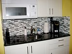 Granite countertop, Keurig coffee maker and fully loaded kitchen area