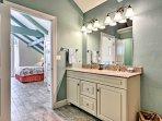 The en-suite bathroom of the master has dual sinks, granite countertops, and a large vanity mirror.