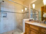 The second guest bathroom is roomy, featuring a large vanity and a stand-alone shower.