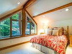 Guest Bedroom 3 is set upstairs in a cozy loft with sloped ceilings and exposed wood beams.