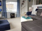 Living room is nicely furnished with sectional that contains comfy full size bed for 2