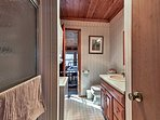 The downstairs bathroom is equipped with a single vanity, walk-in shower, and in-unit laundry machines.