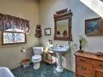 Wash up in the second bathroom, which features a large tub and single vanity.