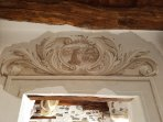 Antique fresco above door leading to small lounge showing San Giulio's arrival.