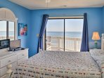 The master bedroom offers a queen-sized bed and direct access to the balcony.