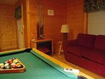 Lower level game room with POOL TABLE, sleeper sofa and door to a covered deck with rockers