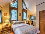 This bedroom features chalet-style windows and tall vaulted ceilings.