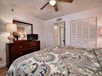 1st guest room has flat screen TV, dresser and closet.