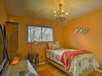 Colorful and cozy, the second bedroom includes a twin-bed and an ornate chandelier.