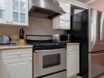 Fully stocked kitchen with stainless steel appliances and granite counters