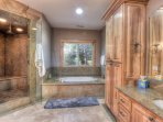 En suite bathroom with standing steam shower and bathtub