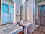 The exquisite master bathroom, made of red tiles and ceramic, has two sinks and a stand-alone shower.
