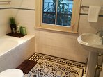 Original Victorian décor vanity unit and MOSIAC flooring. Full shower and bathtub in one.