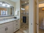 Luxurious shower with tile and hand held shower.  Granite countertops and large mirror.