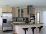 Kitchen with cook top, oven, microwave, ice maker, blender coffee maker, toaster and dishes.