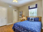 Let the guests wind down and enjoy the queen bed in this cozy guest bedroom with private bathroom