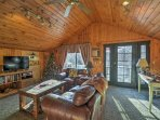 The interior of this cabin is adorned with vaulted ceilings, western decor and a wood-burning stove fostering a cozy...