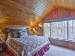 This light and airy bedroom houses a king bed a large picture window that reveals tranquil tree-lined views.