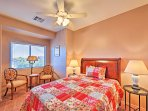 Colorful linens on the queen bed and 2 quaint chairs are found in this room.