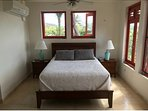 Master bedroom bed with screened windows and AC
