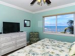 Master bedroom with king-size bed, TV, large bay window overlooking beach and Gulf, walk-in closet