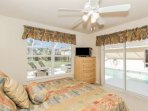 Well decorated guest (queen bed) bedroom w/TV provides direct pool access.