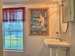 Located just off of the bedroom, the bathroom is home to unique works of art.
