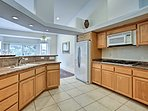 The kitchen features modern appliances and a 2-person eating counter.