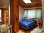Second-floor bedroom with half-bath and back deck overlooking the hillside and.