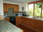 Kitchen with large windows looking out into garden with mature trees and plenty of birds!