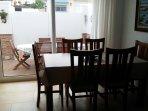 Comedor con cristalera de acceso al patio. Mesa de 6 personas. Extraible hasta 10 comensales.