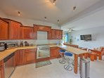 The kitchen features stainless steel appliances and 4-person island peninsula.
