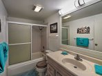 Freshen up in the bathroom with a shower/tub combo.