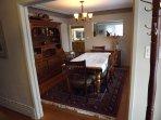 Luxury dining room with custom table and side cabinet, inlaid hardwood floors, custom ceilings