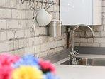 Caldera de gas central en la cocina, sin límite de agua caliente.