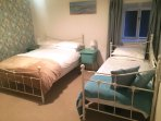 Bedroom with double bed & single daybed.  Storage drawers and wardrobe, Cot, TV, games console.